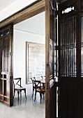Filigrane Holzstühle in Essraum mit großem Wandgemälde; im Vordergrund eine antike, chinesische Holztrennwand mit großer Flügeltür