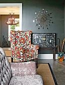 Eclectic mixture of styles with black, Chinese-style cabinet, sunburst mirror and reading chair with cheerful upholstery; couch with iridescent velvet cover in foreground
