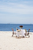 Table set for two with Champagne and flowers on sandy beach