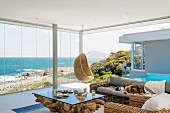 Life by the sea; living room with rustic coffee table, wicker furniture and magnificent view of sea and coast