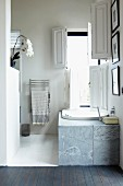 Bathtub with marble surround below bathroom window with open white shutters