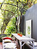 Rustic seating area with furniture made from logs against grey-painted terrace wall