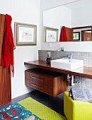 Washstand consisting of exotic wood counter, countertop basin and drawer module in pleasant bathroom