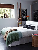 Double bed in front of mirrored sliding wardrobe doors; ethnic-style wooden objets and picture of Native American on wall