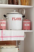 Enamel pots and tins with red lettering on vintage-style kitchen shelves