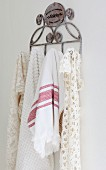 Tea towel and lacy cloths hanging from metal hooks on white wall