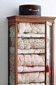 Vintage hatbox on display case with open door and view of stacked bedspreads