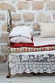 Lace cloth under stacked cushions and blankets on daybed with rusty metal frame against stone wall
