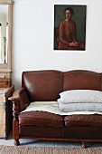 Stacked scatter cushions on traditional, brown leather sofa below painting of woman on white wall
