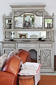 Sofa with brown, leather upholstery in front of traditional dresser painted pale grey with mirrored top against wall