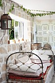 Vintage daybed below window in stone wall in corner of rustic interior