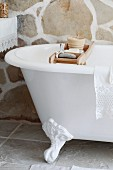 Toiletries on wooden rack over vintage, clawfoot bathtub in rustic bathroom with stone wall