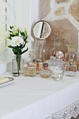 Simple table with white lace cloth and collection of vintage perfume bottles next to vase of flowers and hand mirror in front of stone wall