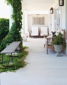 Simple wooden bench on veranda with columns partially covered with climbing plants opposite Colonial-style upholstered bench and loungers