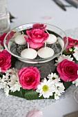 Wasserschale mit Rosenblüte und Schwimmkerzen in einem Blätterkranz mit Rosen und Margeriten
