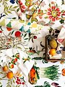 Farbenfrohe Tischwäsche und Papierrollen mit Blumen-, Obst- und Gemüsemotiven