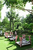 Cheerful daybeds with striped textiles in well-kept garden