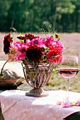 Summer bouquet of dahlias and heather and glass of red wine on garden table