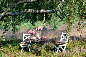 Garden table set with bundt cake and summer flowers below birch tree