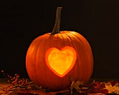 A pumpkin lantern carved with a heart