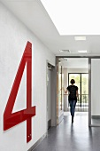 Woman walking along corridor of Kingston University, Faculty of Business, Kingston upon Thames, England