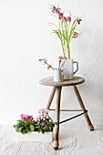 Still-life of old stool and plants (snakes'-head fritillary, fragrant viburnum, primula and cyclamen)
