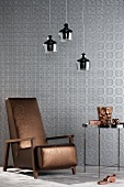 Reading chair with metallic brown cover against silver wallpaper and below three chrome pendant lamps