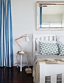 Bedroom on mezzanine with blue and white striped curtain and large, shabby-chic mirror on wall above white double bed