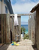 Flippers in weathered outdoor shower area; view of sea through open gate