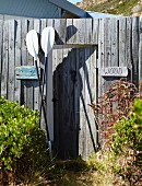 Paddles leaning against weathered garden fence with open garden gate