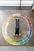 Business man lying in circle of colour cards
