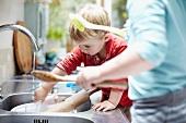 Kinder waschen Geschirr zusammen