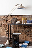 Ornaments on console table, stainless steel standard lamp, basketwork side table and Dutch-style floor tiles