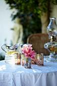 Gedeckter Tisch mit Öllampe, Windlichtern, Blumen und Limonadenkrug