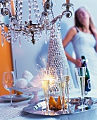 Champagne flutes & sparklers on tray below chandelier with party guest in background