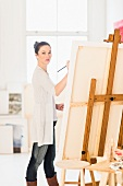 Woman painting picture on easel in artist's studio
