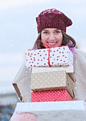 Woman carrying stack of Christmas presents