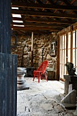 Red-painted wicker chair on stone flagged floor in interior of rustic Italian farmhouse