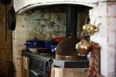 Blaue Emaille Kochtöpfe auf rustikalem Herd in schlichtem Landhaus