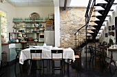 Exposed stone wall, interior staircase, kitchenette and dining table in kitchen