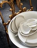 Broken crockery in bowl on antique chair