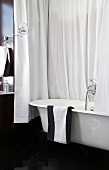 Black and white bathroom with bathtub and shower curtain