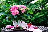 Pinkfarbene Hortensien im Topf und Dessertspeisen auf Gartentisch aus Metall
