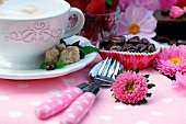 A cup of cappuccino next to dessert cutlery and coffee beans in paper cases on a decorated garden table