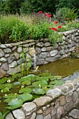 Flowering water lilies in stone-walled pool with terracotta animal head as water spout