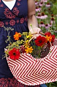 Woman gathering summer flowers in bag