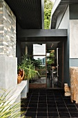 Entrance area with black tiled floor and view into foyer of contemporary house through glass door