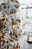 Christmas tree made of twigs and white-painted fern leaves with fairy lights