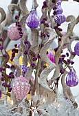 Christmas arrangement of spiral twigs and purple baubles