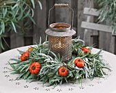 Lantern in centre of winter wreath of eucalyptus leaves and fruits on terrace